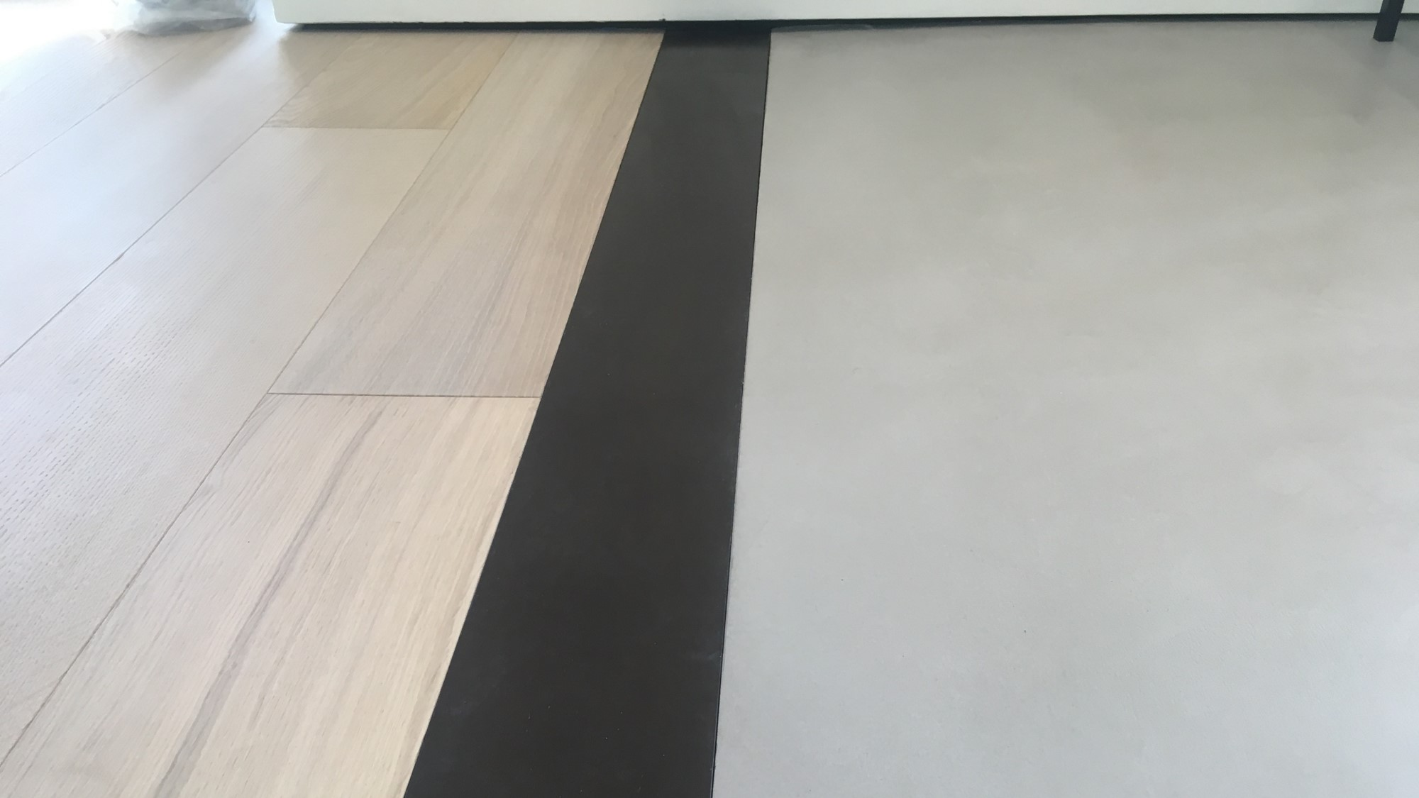 Polished concrete microtopping floors meets wooden floors at luxury apartment in London Marylebone by Polished Concrete Specialists